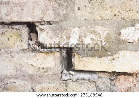 Close up of part of a damaged brick wall - stock photo