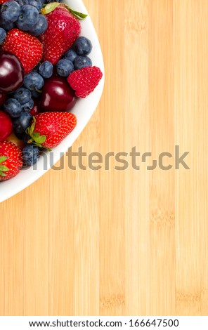 Close up of part of plate full of berries on the table. Concept of healthy eating and dieting lifestyle