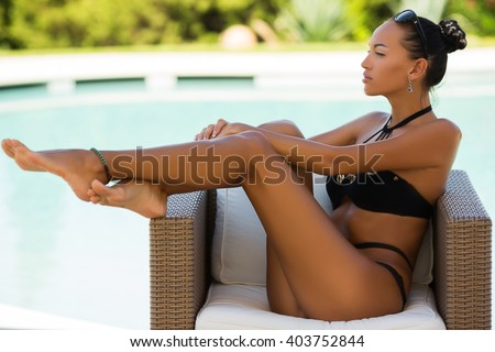 close up of parts of the body, luxury sexy young woman in bikini with many accessories, chains, and jewelry is posing in the swimming pool - stock photo