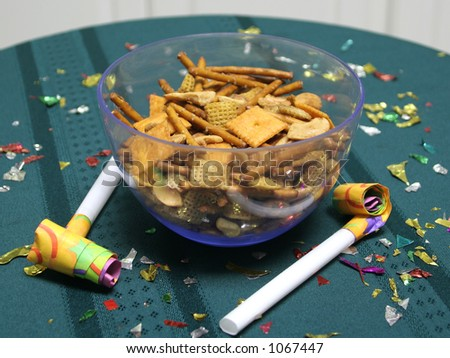 Close up of party blowers on a teal tablecloth, with snack mix and confetti - stock photo