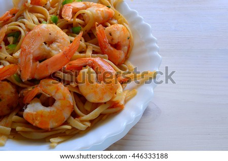 Close up of pasta with prawn on wooden background  with copyspace - stock photo