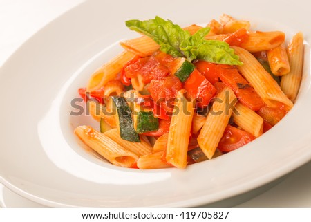 close up of pasta with tomatoes, zucchini and basil on a white plate