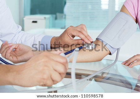 Close-up of patient�¢??s arm during blood pressure measuring at medical consultation - stock photo