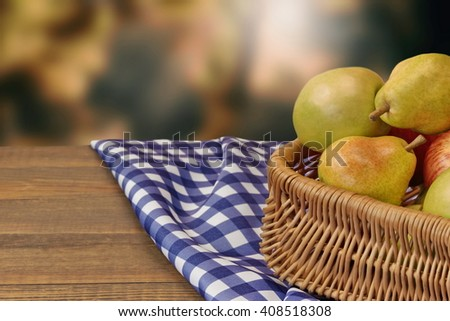 Close Up Of Pears And Apples In Wicker Basket  On The Rustic Wood Table With Checkered Blue Tablecloth. Garden In The Blurred Background - stock photo