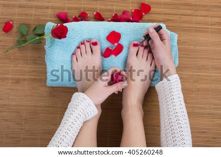 Close-up of pedicurist applying nail polish to the toenails - stock photo