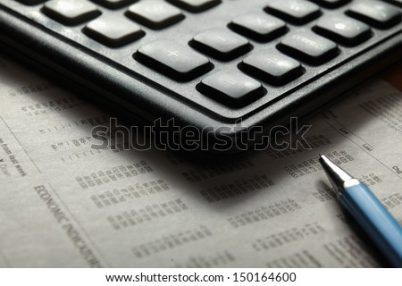 Close-up of  pen and calculator on paper table numbers. - stock photo
