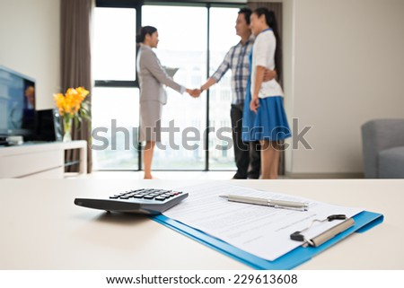 Close-up of pen, contract, calculator on the table and estate agent making a deal in the background - stock photo
