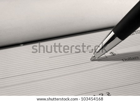 Close up of pen filling out a personal bank check with copy space. - stock photo