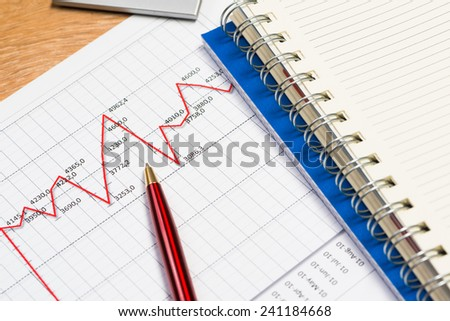 close-up of pen, notebook and graph growth - stock photo