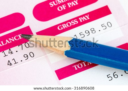 Close up of pencil and wage slip - stock photo
