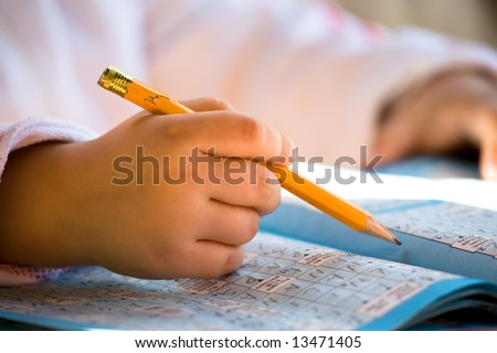 Close up of pencil in child hand over crossword. Very shallow DOF. - stock photo