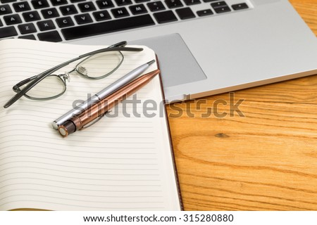 Close up of pens, selective focus on pens, with open blank notebook, reading glasses, and computer in background on desktop.  - stock photo