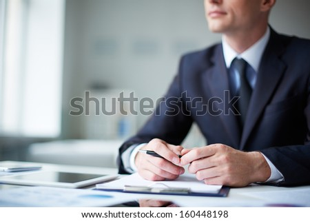 Close-up of pensive male hands with pen over document