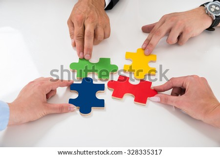 Close-up Of People Assembling Colorful Puzzle Pieces At Desk