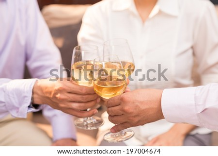 Close-up of people clinking glasses with white wine - stock photo