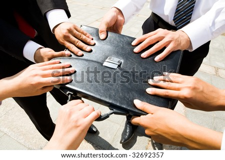 Close-up of people hands holding black leather briefcase simultaneously