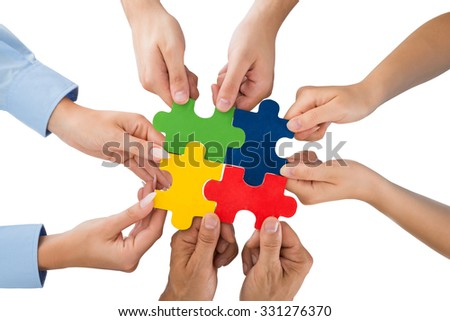 Close-up Of People Hands Holding Jigsaw Pieces Over White Background