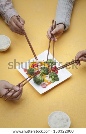 Close up of people holding chopsticks and sharing one dish - stock photo