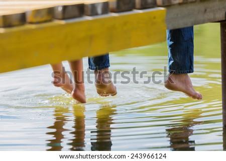 Close up of people's feet sitting on bridge - stock photo