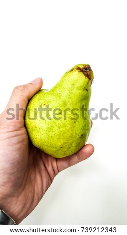 Close-up of people's hand holds a green pear on white background