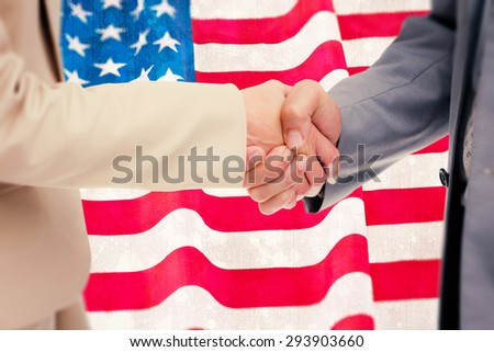 Close up of people shaking hands against paint splattered paper