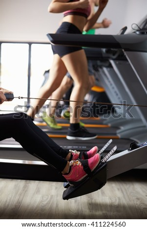 Close Up Of People Using Equipment In Busy Gym