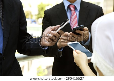 Close up of people with contemporary mobile phones
