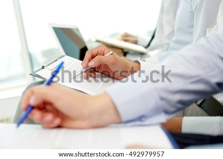 Close-up of peoples hands making written review of planned work