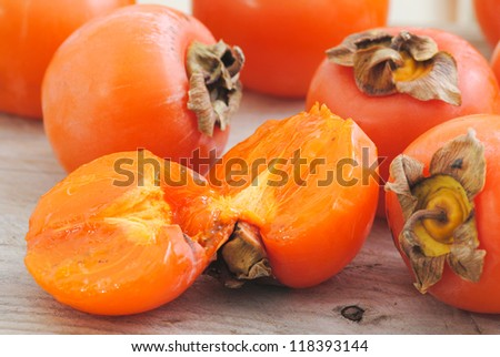 Close up of persimmon fruits. Fuyu, Persimmons fruits hall and halves on rustic white wood background.Winter fruit. - stock photo