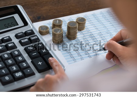 Close-up Of Person Analyzing Financial Report With Stack Of Coins