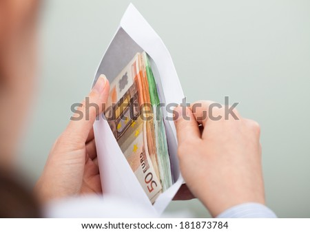 Close-up Of Person Checking Out Envelope With Cash - stock photo