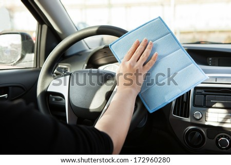 Close-up Of Person Cleaning Steering Wheel In Car - stock photo
