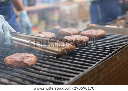 Close Up of Person Cooking Burger Patties Using Tongs on Smoking Barbecue Grill - stock photo