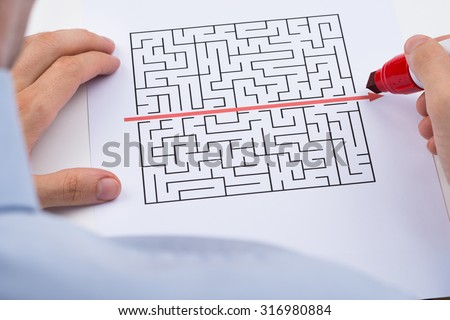 Close-up Of Person Drawing Straight Red Line Over Maze With Red Marker