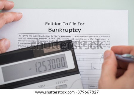 Close-up Of Person Hand And Calculator Over Bankruptcy Form