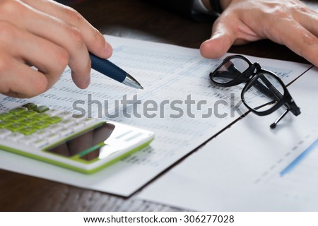 Close-up Of Person Hand Calculating Finance With Glasses At Desk - stock photo