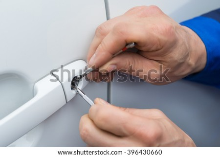 Close-up Of Person Hand Holding Lockpicker To Open Car Door - stock photo