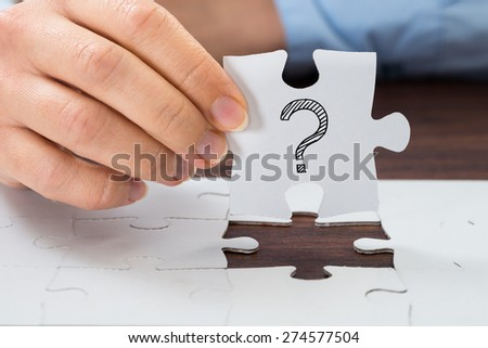 Close-up Of Person Hand Holding Puzzle With Question Mark Sign - stock photo