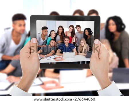 Close-up Of Person Hand Photographed Group Of Student Studying In College - stock photo
