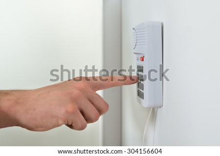 Close-up Of Person Hand Pressing Button On Door Security System - stock photo