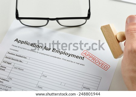 Close-up Of Person Hand With Rubber Stamp And Approved Employment Application Form - stock photo