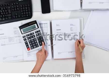 Close-up Of Person Hands Calculating Receipts At Desk - stock photo