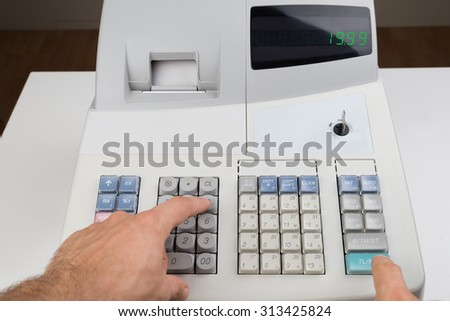 Close-up Of Person Hands Entering Amount On Cash Register - stock photo