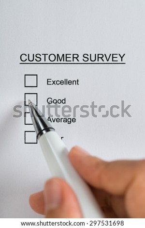 Close-up Of Person Hands Filling Customer Survey Form With Pen - stock photo