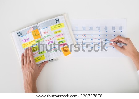 Close-up Of Person Hands Highlighting Date On Calendar With Diary At Desk - stock photo