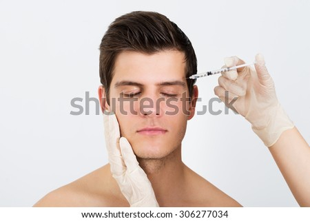 Close-up Of Person Hands Injecting Syringe With Botox For Face Treatment - stock photo