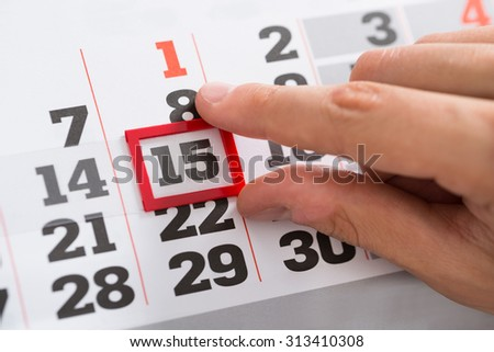 Close-up Of Person Hands Making A Red Mark On Calendar Date - stock photo