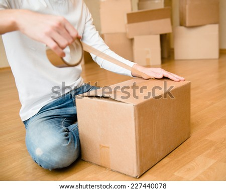 Close up of person hands packing cardboard box - stock photo