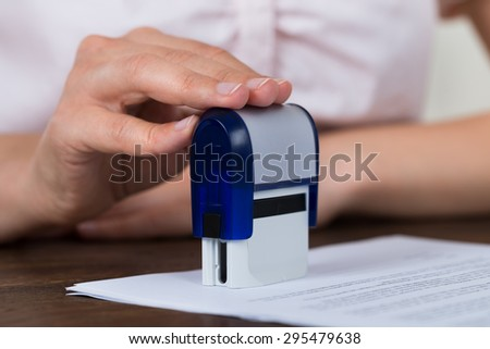 Close-up Of Person Hands Stamping Document At Desk - stock photo