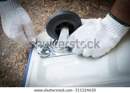Close-up Of Person Hands Tightening Bolt Of Bicycle Tire With Wrench - stock photo